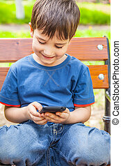 boy playing games on smartphone - Happy little boy smiling...