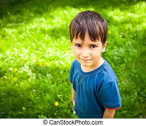 Cute boy standing on grass - Cute boy standing against green...