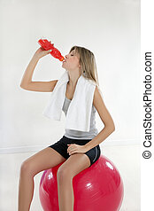 fitness and yoga - young woman sitting on fitness ball in...