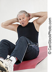 fitness and yoga - senior man doing abs exercise in health...