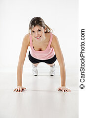 fitness and yoga - front view of young woman doing push-ups