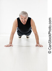 fitness and yoga - front view of senior man doing push-ups