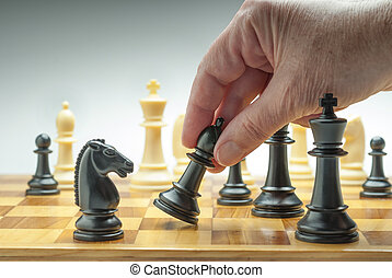 Chess conflict - Hand moving a chess piece on board as a...
