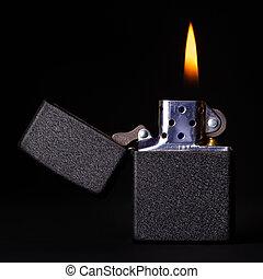 Burning Lighter - black gasoline lighter with flame on dark...