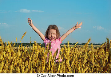 Happy girl in wheat field with her hands up