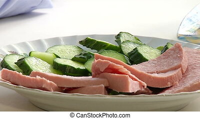 Sliced sausages and cucumbers on a plate