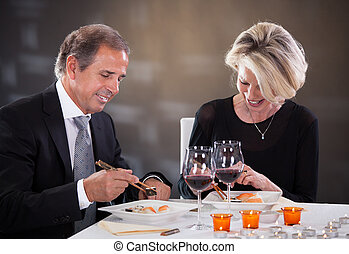 Mature Couple Sitting In A Restaurant - Happy Mature Couple...