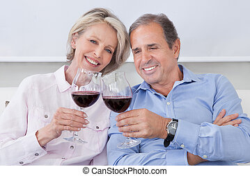 Portrait Of Mature Couple Toasting With Wine - Portrait Of...