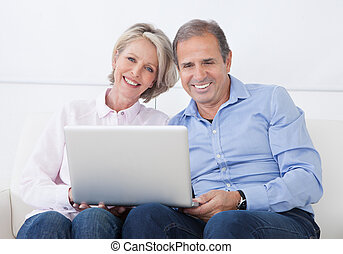 Happy Mature Couple Working On Laptop - Happy Mature Couple...