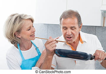 Happy Mature Couple Cooking Food In Kitchen - Man Looking At...