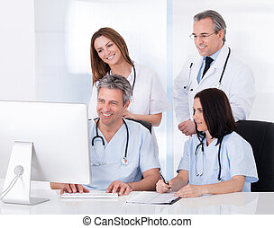 Group Of Doctors Working Together - Female And Male Doctors...
