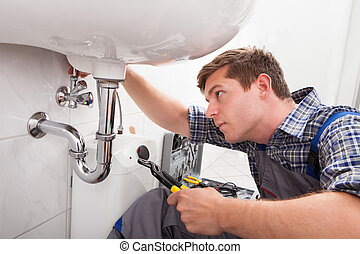 Young plumber fixing a sink in bathroom - Portrait of male...