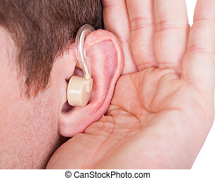 Man Wearing Hearing Aid And Listening For A Quiet Sound -...