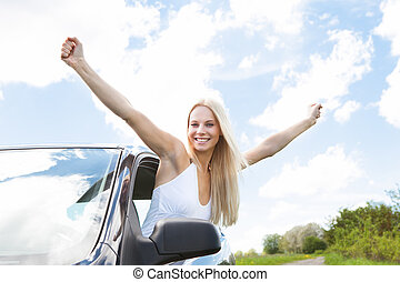 Woman Raising Hand Out Of Car Window - Happy Young Woman...