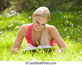 Young Beautiful Woman Lying On Grass Writing In Diary -...