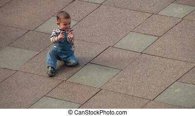 Baby crawling on all fours on the granite pavement