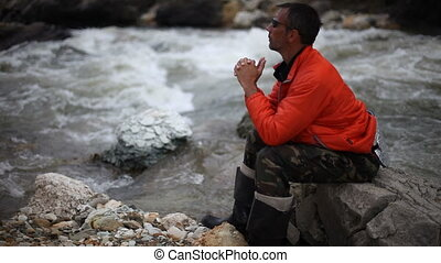 Man sitting on trunk on mountain trail. Mountain stream with stones