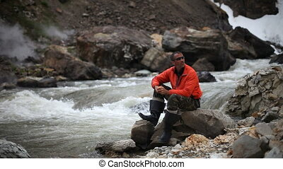 Man sitting on trunk on mountain trail. Mountain stream with...