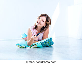 cute girl watching TV lying on the floor
