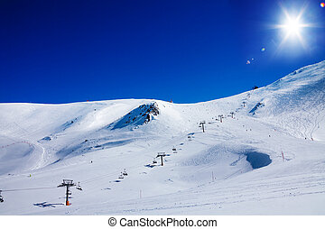 Ski lift in Andorra - Ski lift lifting skiers on top of high...