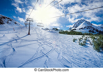 Ski lift with seats going over the mountain and paths from...