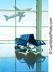 Airport terminal - Seats in airport terminal with airplane...
