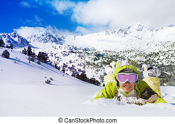 Skier laying in snow - Young smiling woman in ski glasses...