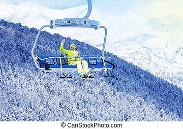 Happy skier in on the ski lift waiving hand - Happy skier...