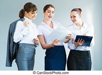 group of business women discussing documents together,...
