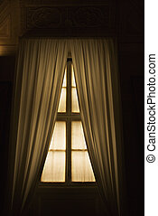 Interior window with drapes. - Dimly lit window with drapes...