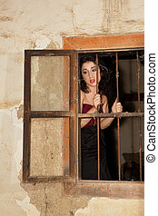 Melancholic woman behind bars of a derelict building