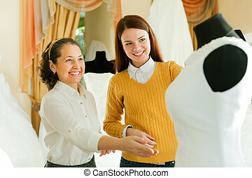 Mature woman with girl chooses white gown - Mature woman...