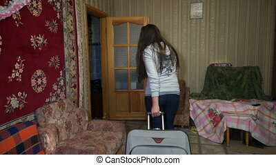 A woman with a suitcase out of the house