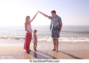 young family by the sea - young family stands as a house by...
