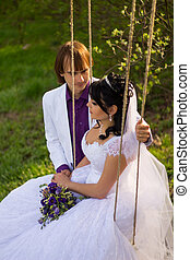bride and groom swinging on a swing