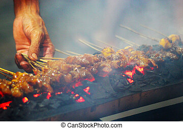 Grilled satay on the streets - A market seller grilling meat...