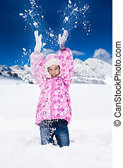 Girl throw snow - Little happy smiling girl in pink throws...
