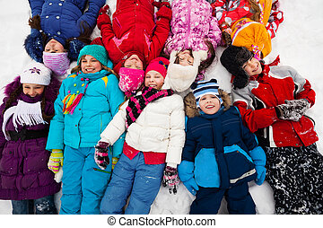 many kids in snow - Large group of kids laying in snow...