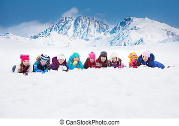 Large group of kids laying in snow - Large group of...