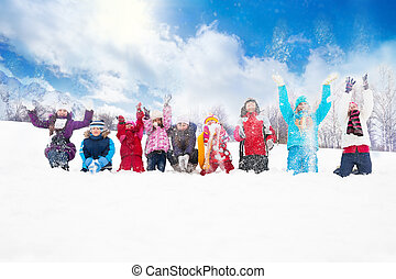 Group of kids throwing snow in the air - Large group of...