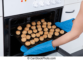 Woman Placing Cookies In Oven