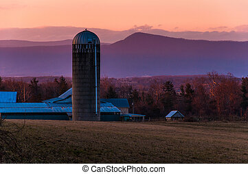 Barn and silo on a farm in the Shenandoah Valley at sunset,...