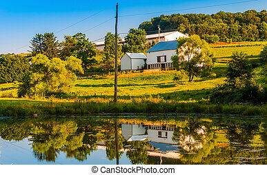 Barn and trees reflecting in a small pond on a farm in rural York County, Pennsylvania.