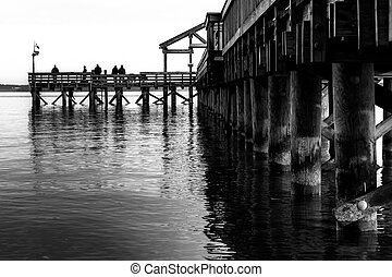 Black and white image of a fishing pier extending into the...