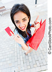 Paying With Card - Brunette woman holding a red credit card...