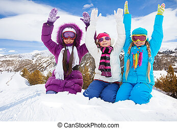 Hooray, winter fun - Three happy girls lifting hands sitting...