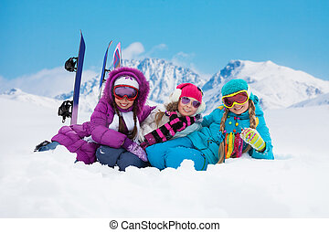 Ski vacation - Three girls with snowboards laying on the...
