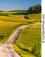 Country road and farm fields on a large hill in rural York County, Pennsylvania.