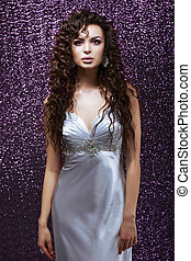 Sophistication. Glamor. Sensual Brunette with Waved Hairs and Silk Blue Dress