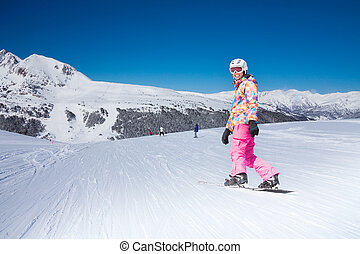 Woman sliding downhill - Young beautiful woman on snowboard...